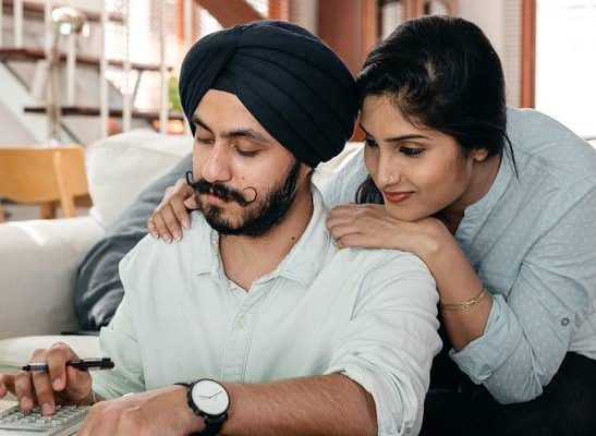 Focused young Indian couple working at home using calculator